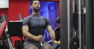 O homem afro-americano novo executa um exercício no simulador vídeos de arquivo