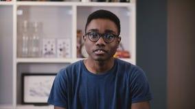 O homem afro-americano novo mostra a emoção diferente Indivíduo preto considerável nos risos dos vidros, então sérios e outra vez vídeos de arquivo