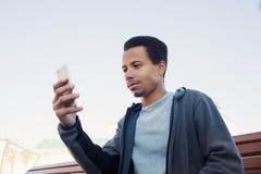 O homem afro-americano novo no desgaste do esporte está usando o smartphone Imagem de Stock Royalty Free