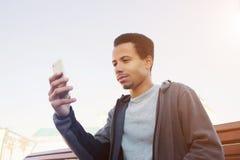 O homem afro-americano novo no desgaste do esporte está usando o smartphone Imagens de Stock