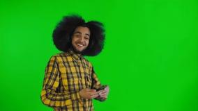 O homem afro-americano que anda no quadro, recebeu uma mensagem nova em seu telefone na tela verde ou no fundo chave do croma filme