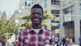 O homem afro-americano sorri e olha direito na câmera Imagens de Stock