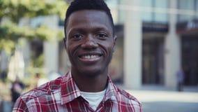 O homem afro-americano sorri e olha direito na câmera Fotografia de Stock Royalty Free
