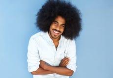 O homem afro de sorriso com braços cruzou-se contra a parede azul fotos de stock royalty free