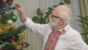O homem agradável idoso pendura o árvore-brinquedo do Natal vídeos de arquivo