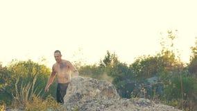 O homem agressivo brutal grita na rocha lentamente filme