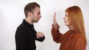 O homem agressivo irritado quer bater sua mulher, ele está gritando Mão do aumento da mulher que mostra o para parar a violência filme