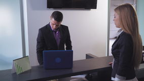 O homem ajuda a fêmea a retirar o dinheiro vídeos de arquivo