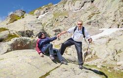 O homem ajuda a mulher a levantar-se de uma pedra Fotografia de Stock Royalty Free