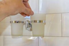 O homem ajusta os copos no suporte no banheiro, no conceito do reparo e na melhoria de casa foto de stock royalty free
