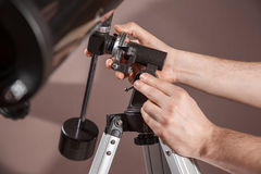 O homem ajusta um close up do telescópio Imagens de Stock