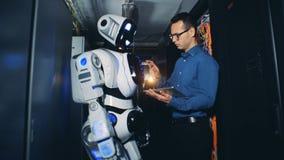 O homem ajusta um programa em um robô em um centro de dados 4K video estoque