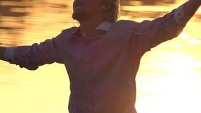 O homem alegre escuta a música em um banco do lago no por do sol no slo-mo vídeos de arquivo