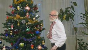 O homem alegre idoso dança perto da árvore de Natal video estoque