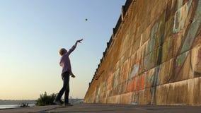 O homem alegre joga uma bola em uma parede do banco de rio no slo-mo filme
