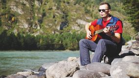 O homem alegre novo que veste óculos de sol que os jogos em uma guitarra cantam a música senta-se ao lado do rio da montanha no d video estoque