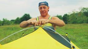 O homem amarra a barraca da barraca aos arcos para prender video estoque