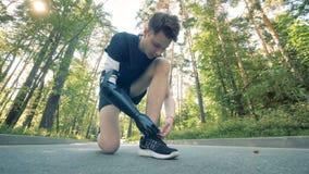 O homem amarra suas sapatilhas com um braço artificial, fim acima Braço robótico futurista do cyborg em um ser humano