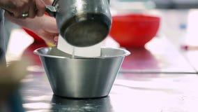 O homem amassa a massa da água e da farinha na cozinha video estoque
