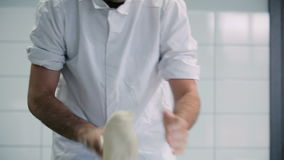 O homem amassa a massa na tabela na cozinha filme