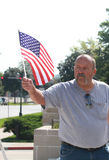 O homem americano acena a bandeira dos E.U. na reunião para fixar nossas beiras Fotos de Stock Royalty Free