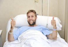 O homem americano novo que encontra-se na cama na sala de hospital doente ou doente mas que dá manuseia acima do sorriso feliz e  imagem de stock royalty free
