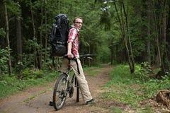 O homem, amigos de espera em uma estrada secundária na floresta Fotografia de Stock Royalty Free