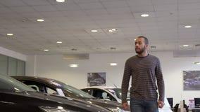 O homem anda ao longo da sala de exposições do carro foto de stock royalty free