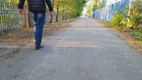 O homem anda ao longo do asfalto video estoque