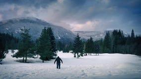 O homem anda através da neve profunda na paisagem congelada video estoque
