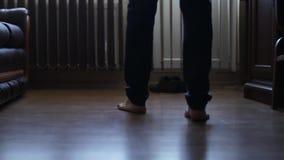 O homem anda com os pés descalços na casa no assoalho de madeira video estoque