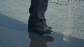 O homem anda perto da fonte, sapatas molhadas, close-up filme