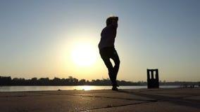 O homem animador dança ativamente em um banco de rio no verão no slo-mo vídeos de arquivo