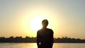 O homem animador joga uma bola acima em um banco de rio no por do sol no slo-mo vídeos de arquivo