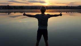 O homem animador mantém o polegar dois acima dos gestos no por do sol no slo-mo filme