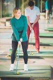 O homem 30-35 anos velho é mulher que 25-29 anos de jogadores de golfe idosos são e Fotos de Stock Royalty Free