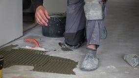 O homem aplica o cimento da colagem na telha do assoalho e do hexágono da configuração vídeos de arquivo