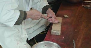 O homem aponta a faca usada para estripar e enfaixar enguias vídeos de arquivo