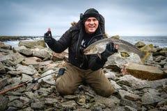 O homem aprecia a pesca do inverno da truta de mar Fotos de Stock Royalty Free