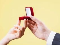 O homem apresenta o anel dourado para a jovem mulher Foto de Stock