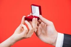 O homem apresenta o anel dourado para a jovem mulher Foto de Stock Royalty Free