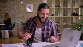O homem apto bonito, aparência caucasiano com barba preta está sentando-se no local de trabalho e está datilografando-se no compu vídeos de arquivo