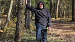 O homem aquece-se no parque na manhã perto da árvore vídeos de arquivo