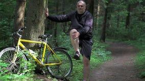 O homem aquece-se perto da bicicleta no parque vídeos de arquivo