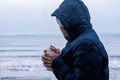 O homem aquece suas mãos com café afastado imagens de stock