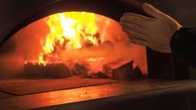 O homem aquece suas mãos pelo fogo Fogo da fornalha Videoclip de lenha ardente na chaminé Queimadura da lenha no filme
