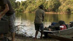 O homem arrasta o barco sobre a costa do lago com bagagens foto de stock royalty free