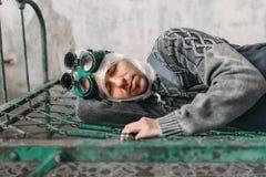 O homem arrepiante envolve sua cabeça no filme e encontra-se na cama Imagens de Stock Royalty Free