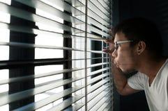 O homem asiático está olhando através de uma janela fotos de stock