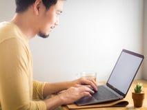 O homem asiático faz o negócio em um portátil na tabela de madeira com um copo de fotos de stock royalty free